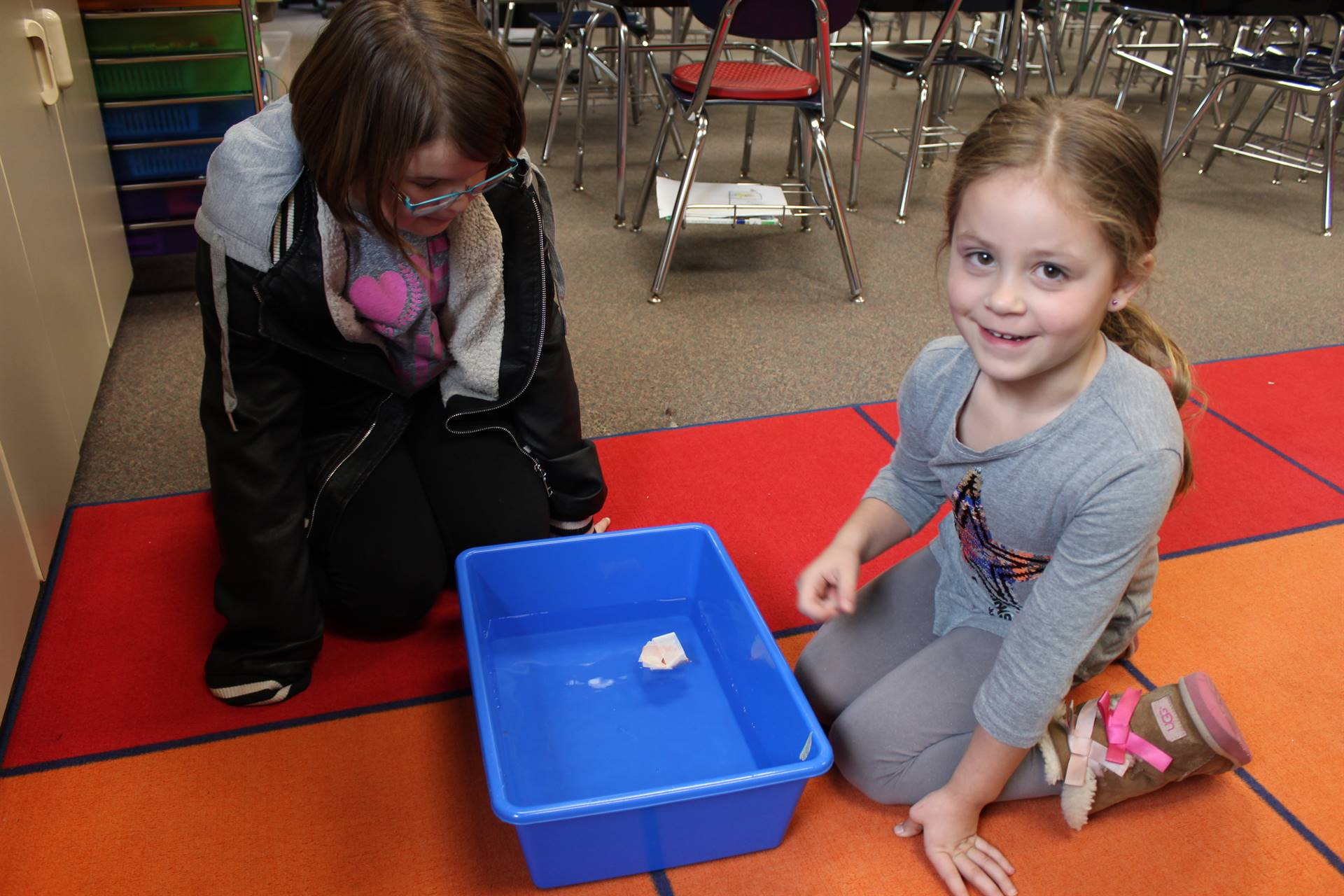 Two students checking out an item to see if it floats
