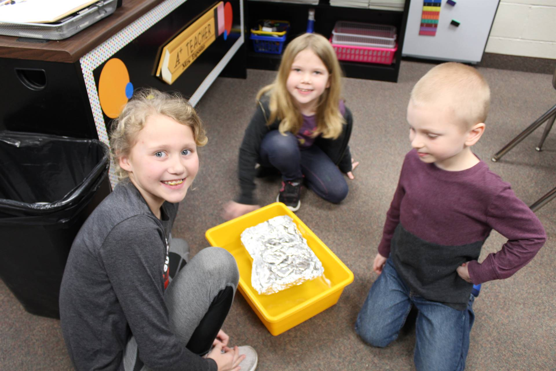 Three students checking out their boat to see if it floats