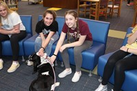 Two students petting a dog
