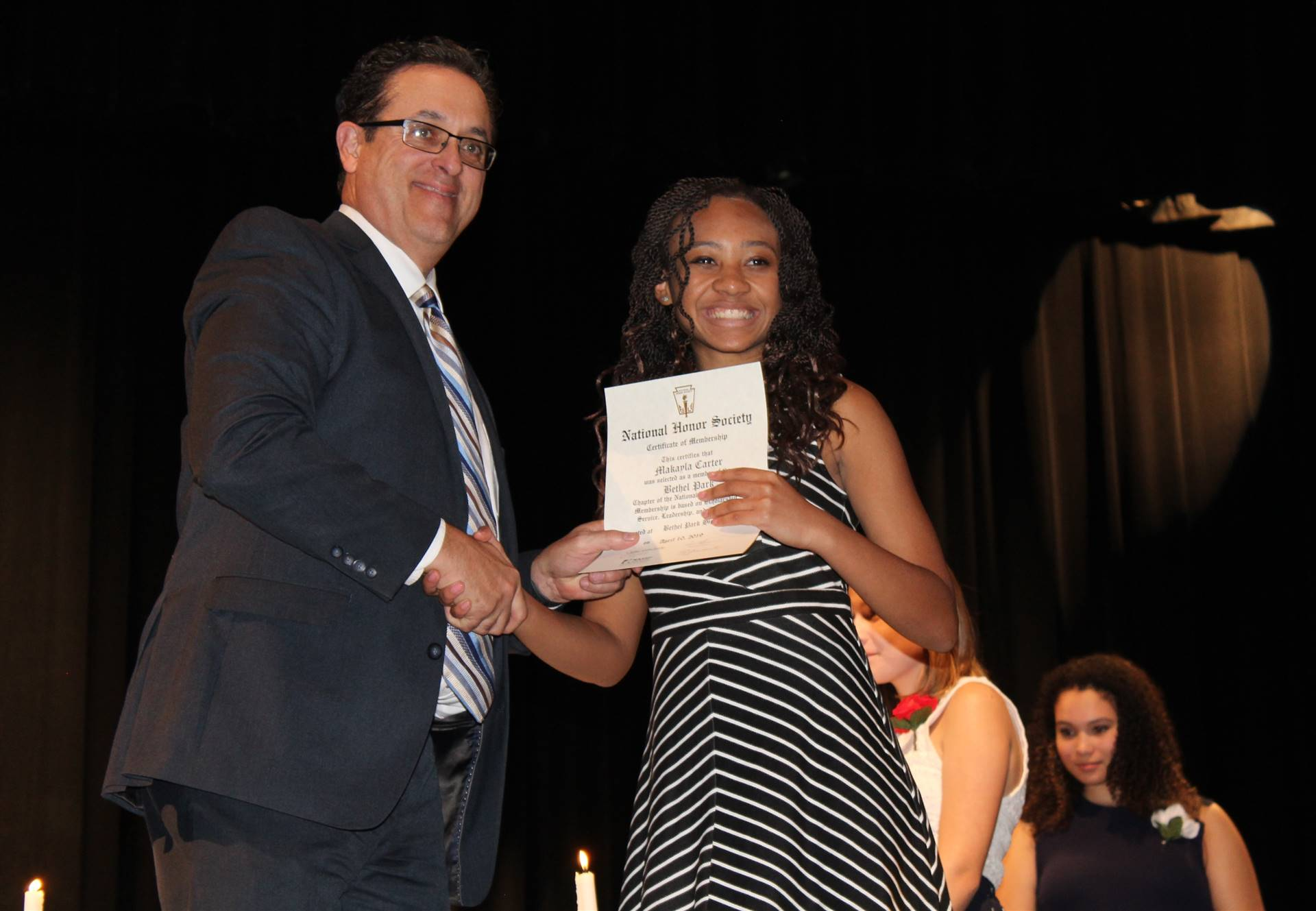 Student receiving her National Honor Society Induction certificate