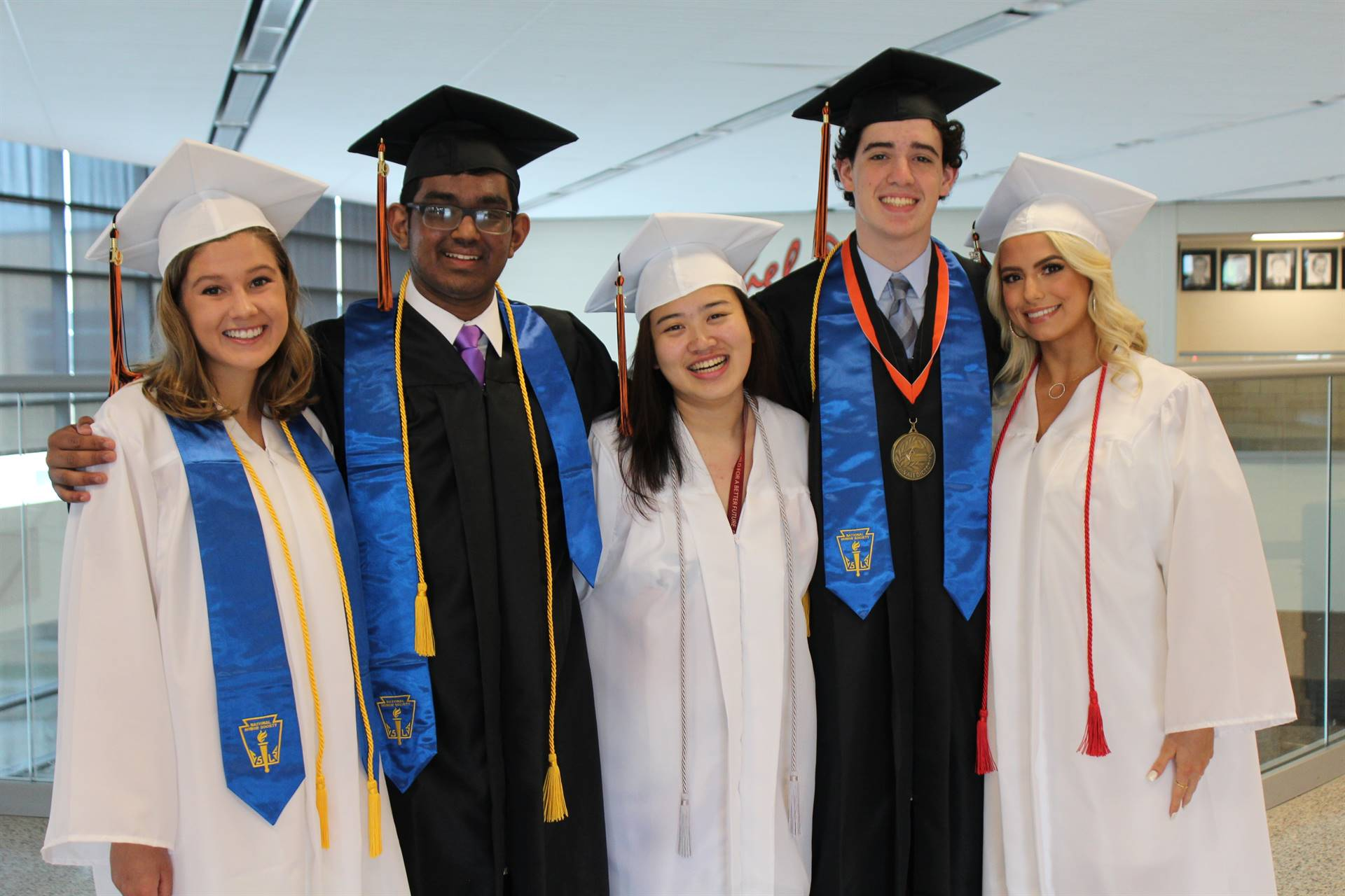 Five members of the Class of 2019 in their caps and gowns