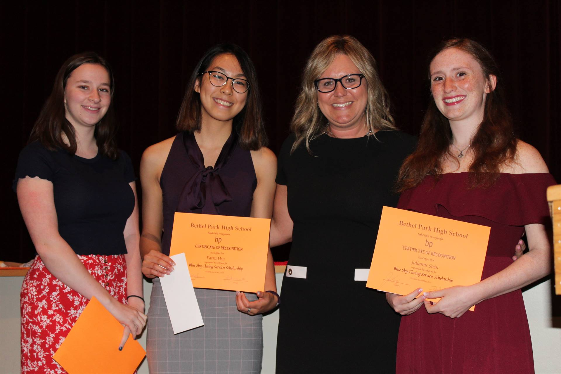 Three students receiving a scholarship