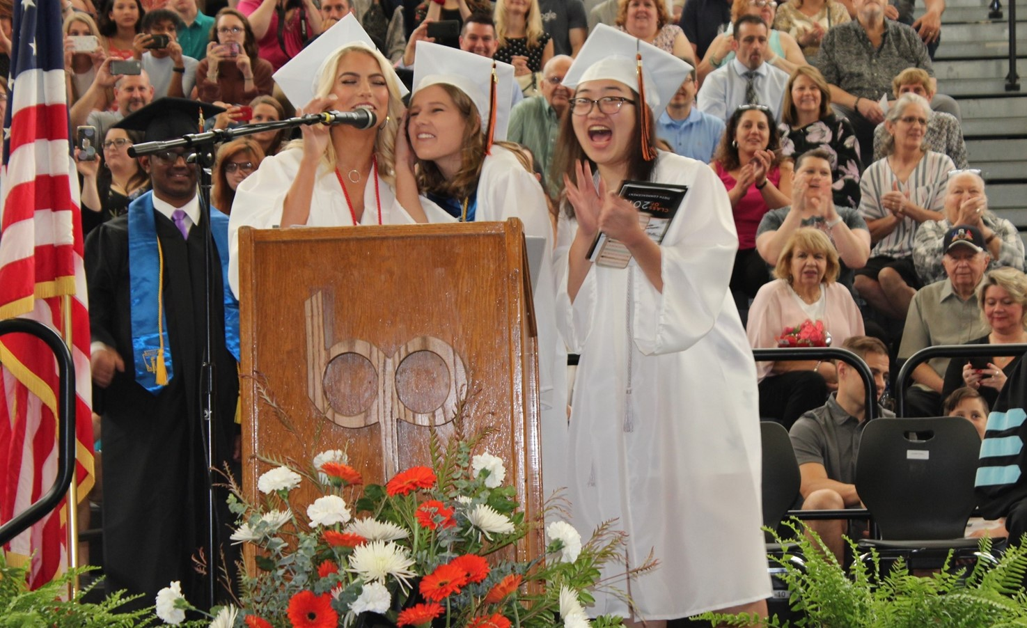 Three students conduct the Tassel Ceremony