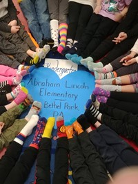 Kindergarten students sitting in a circle wearing crazy socks