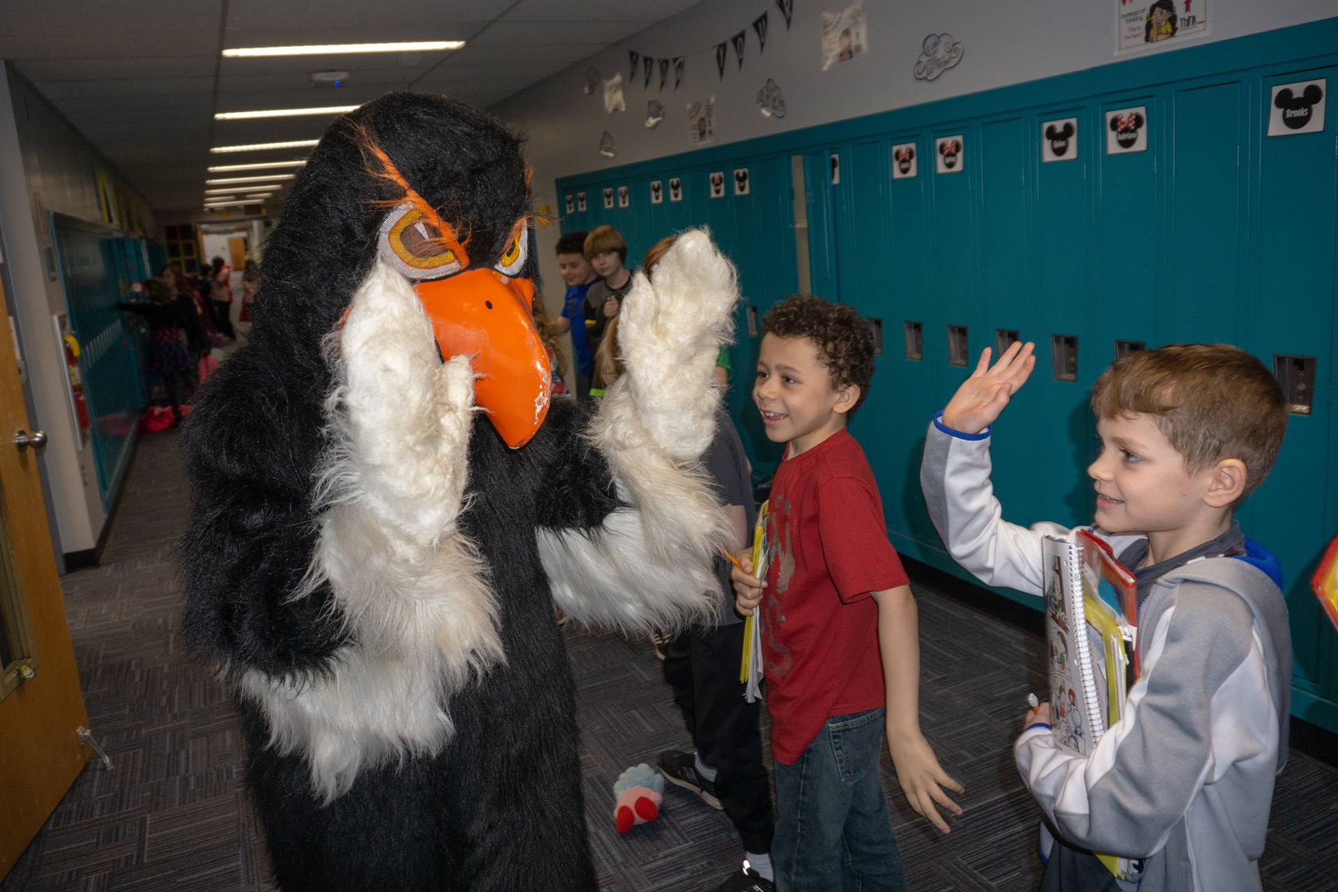 The Hawk high-fiving a student