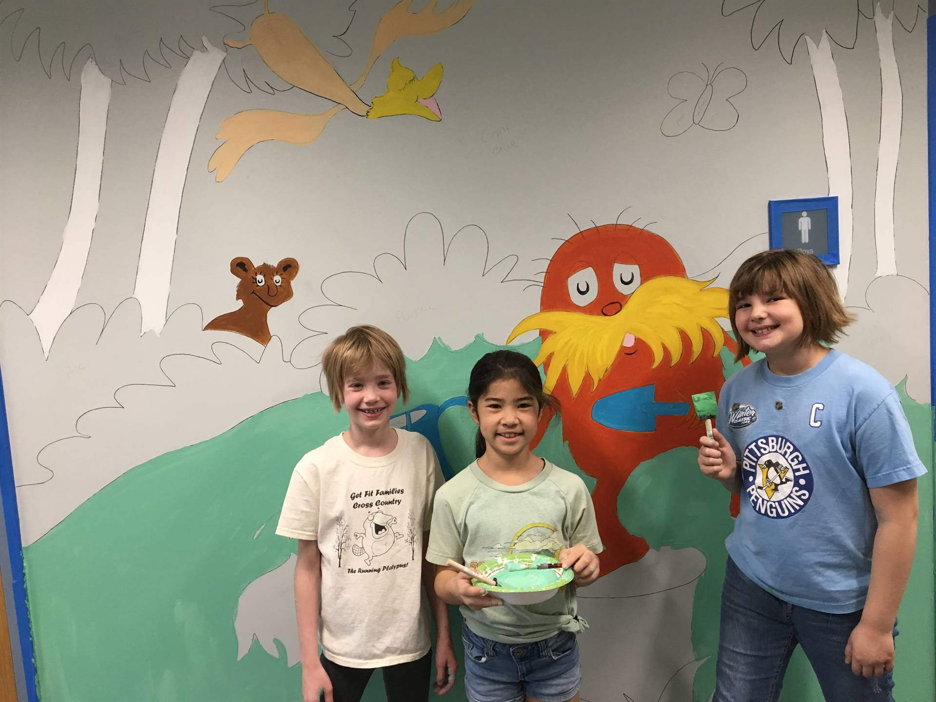 Three students in front of the Lorax mural