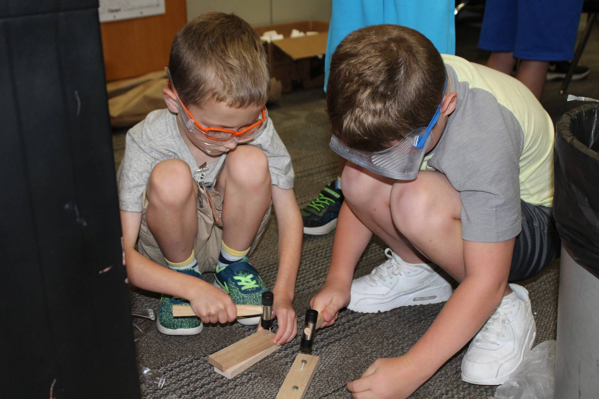 Two students hammering nails into boards
