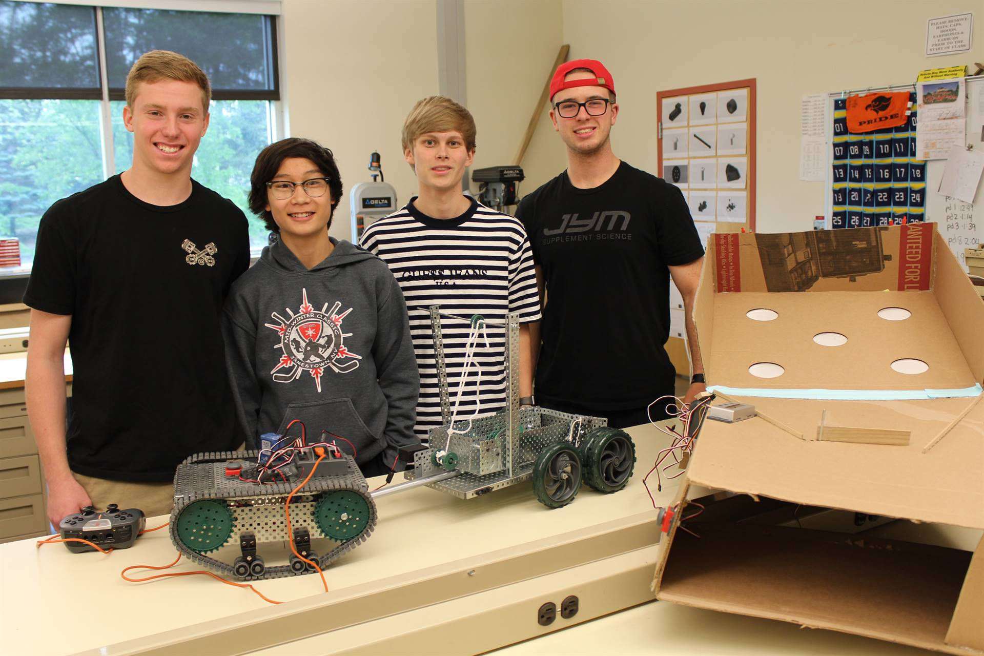 Four students with their Principles of Engineering Class projects