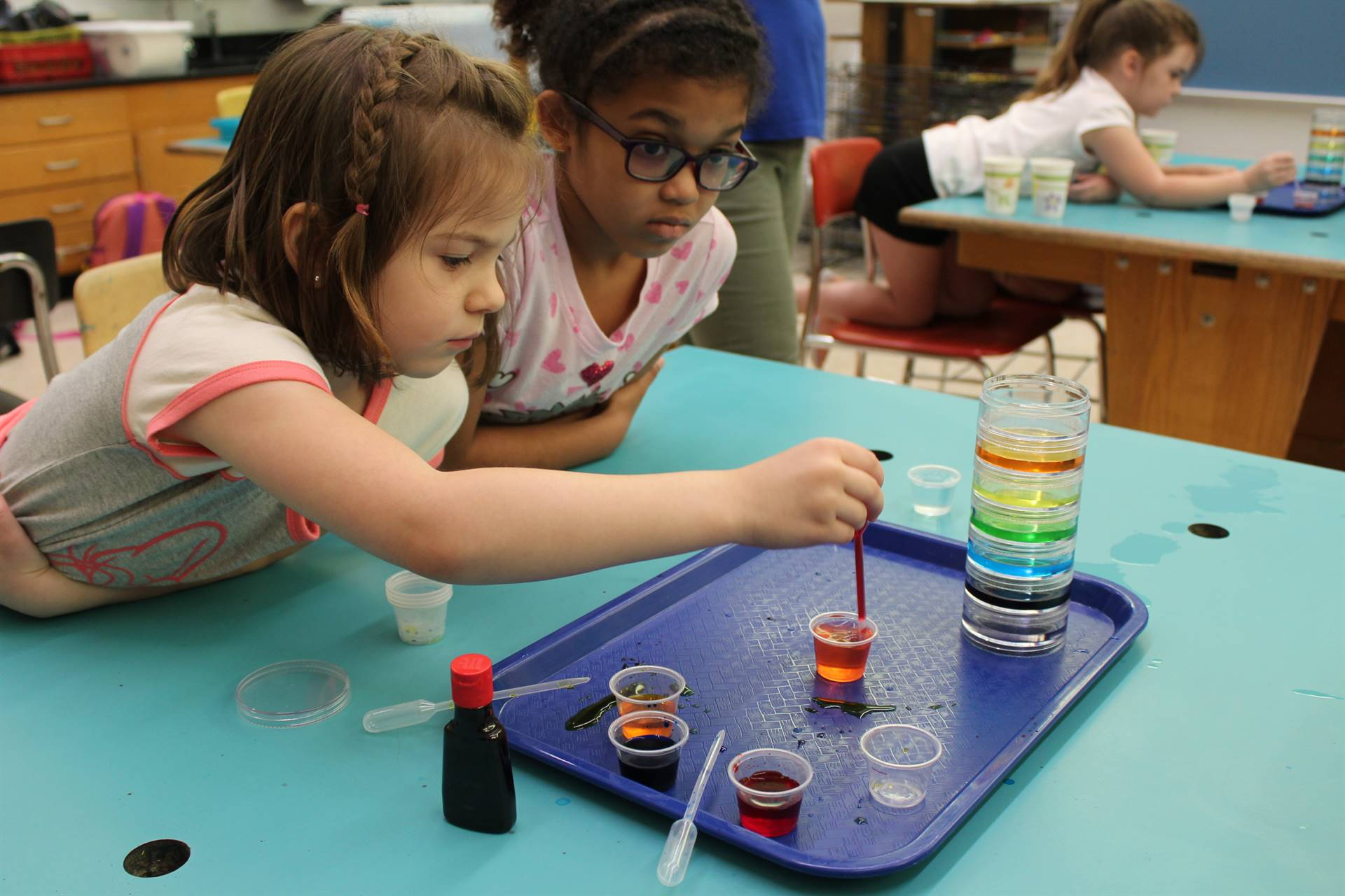Two students working together to create a liquid rainbow