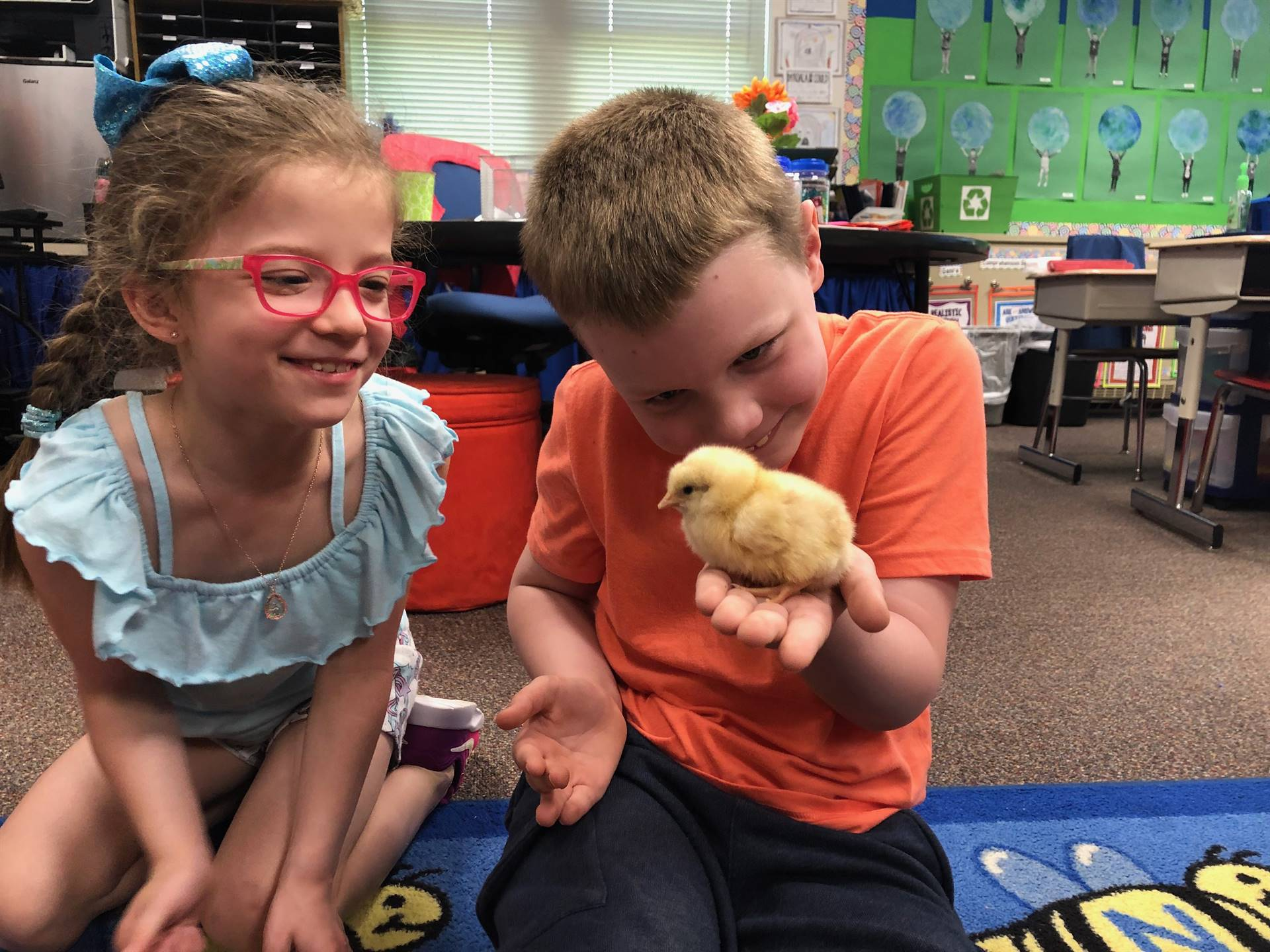 Student holding a chick while another student looks on