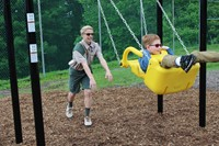 James pushing a student on a swing