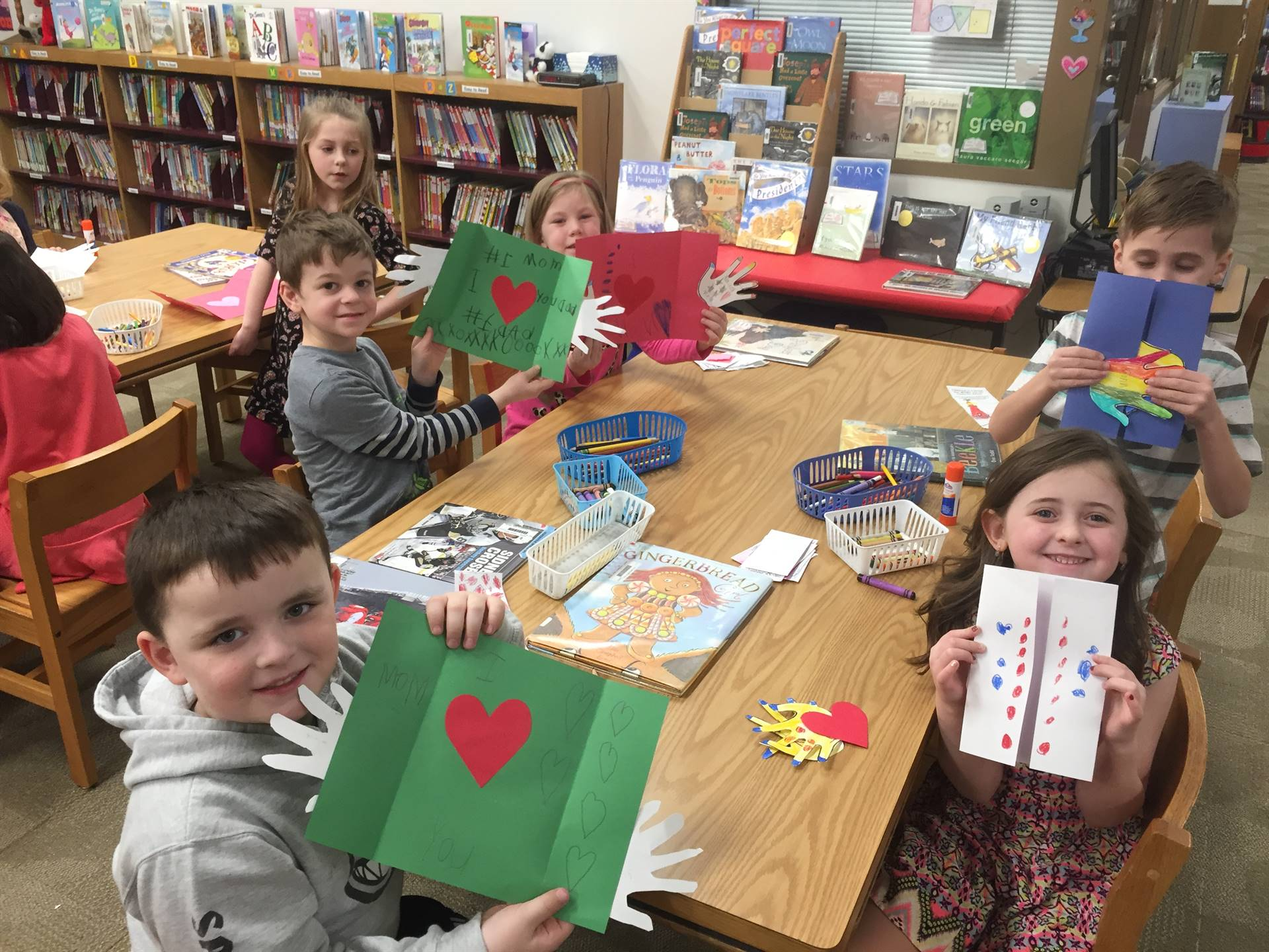 five kindergarten students holding up their Valentines Day cards