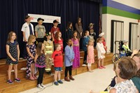 Students singing a song for their parents