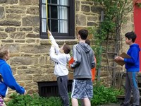 Four students measuring a window at the Homestead