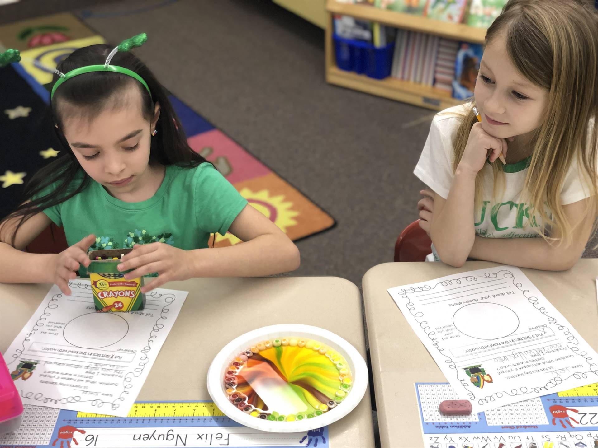 Two students conducting a science experiment with Skittles