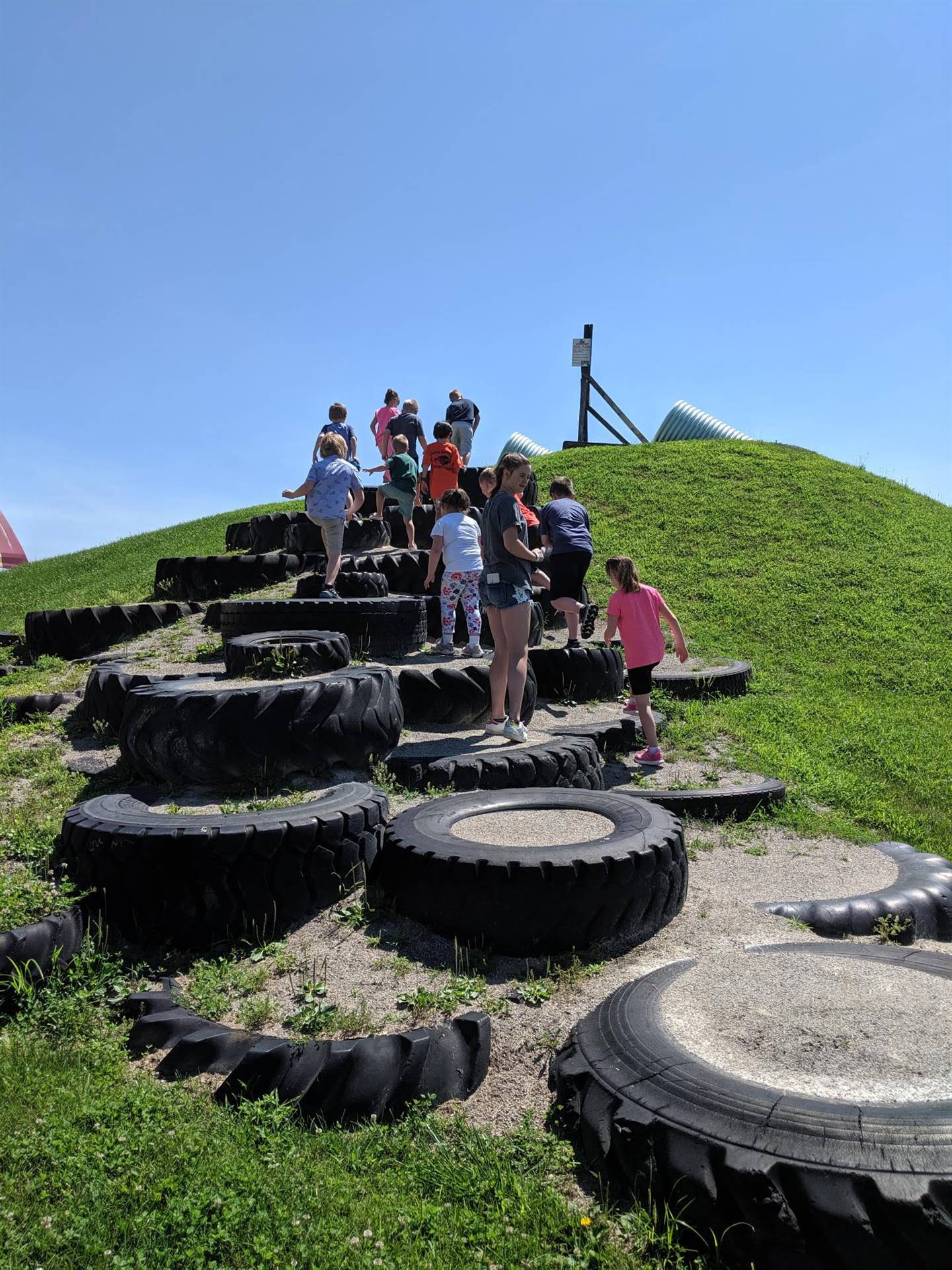 Students walking up a hill paved with tires