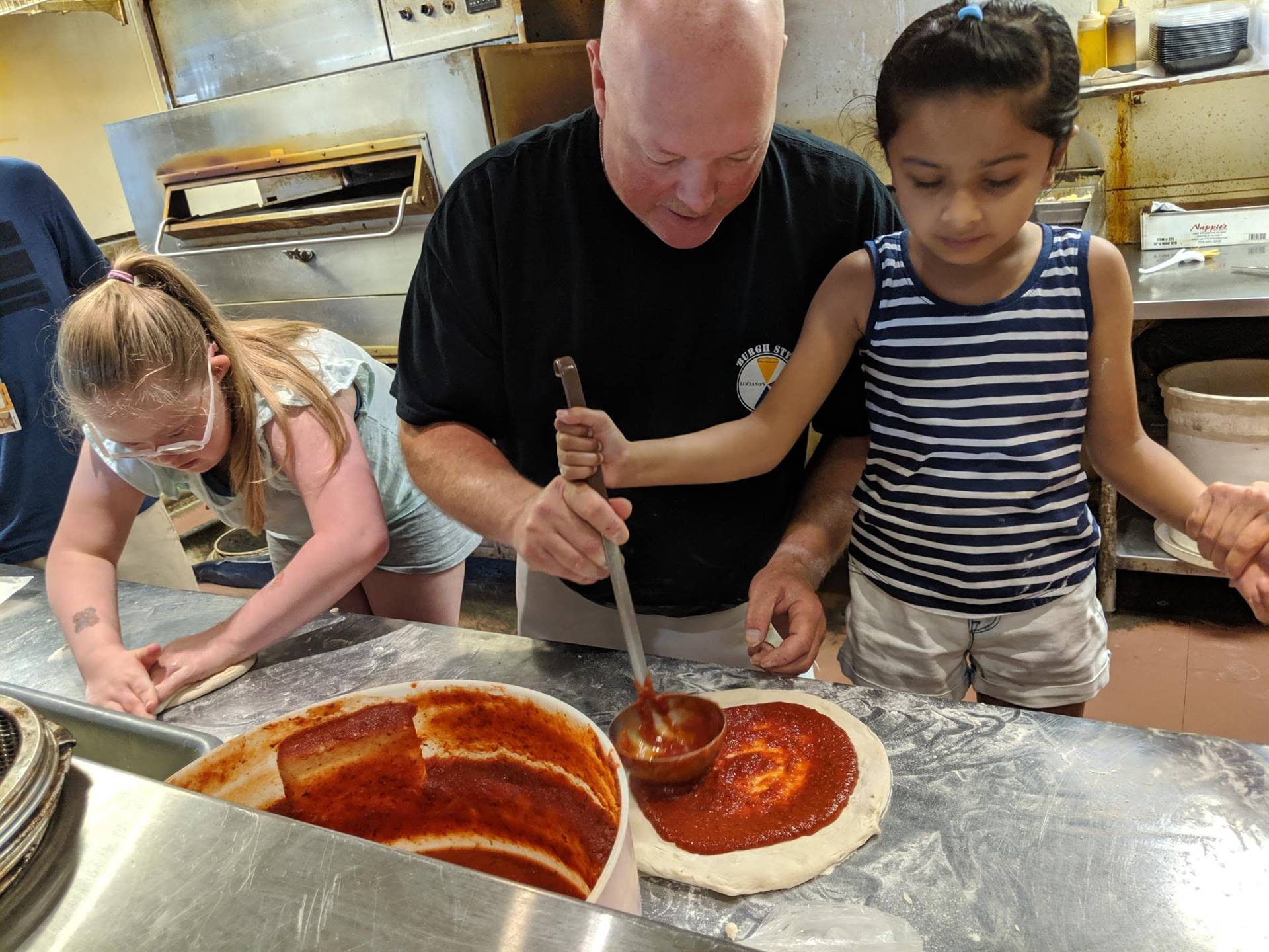 Student spreading sauce on a pizza