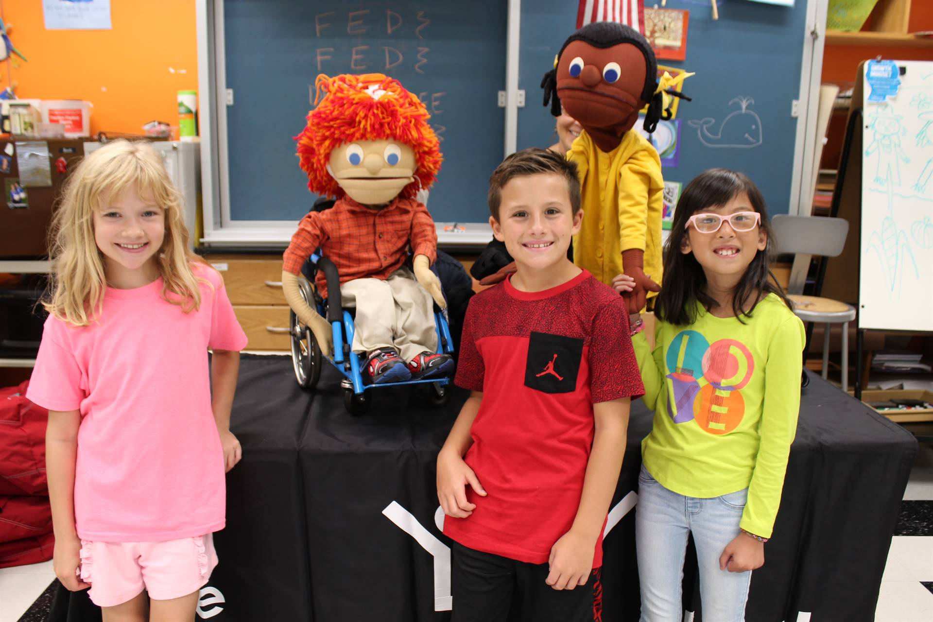 Three students with two puppets