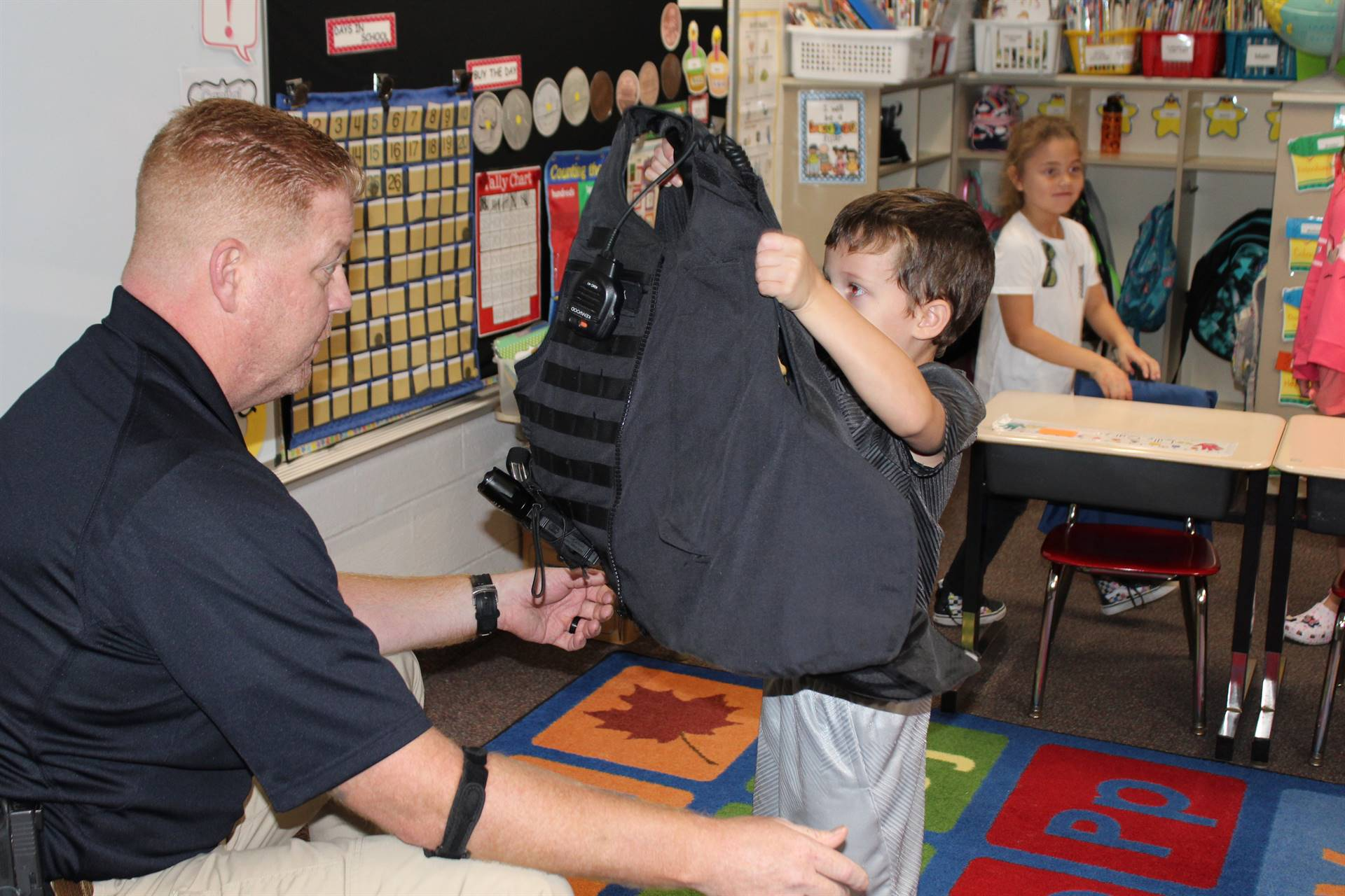 Student holding Officer Ken's bullet proof vest