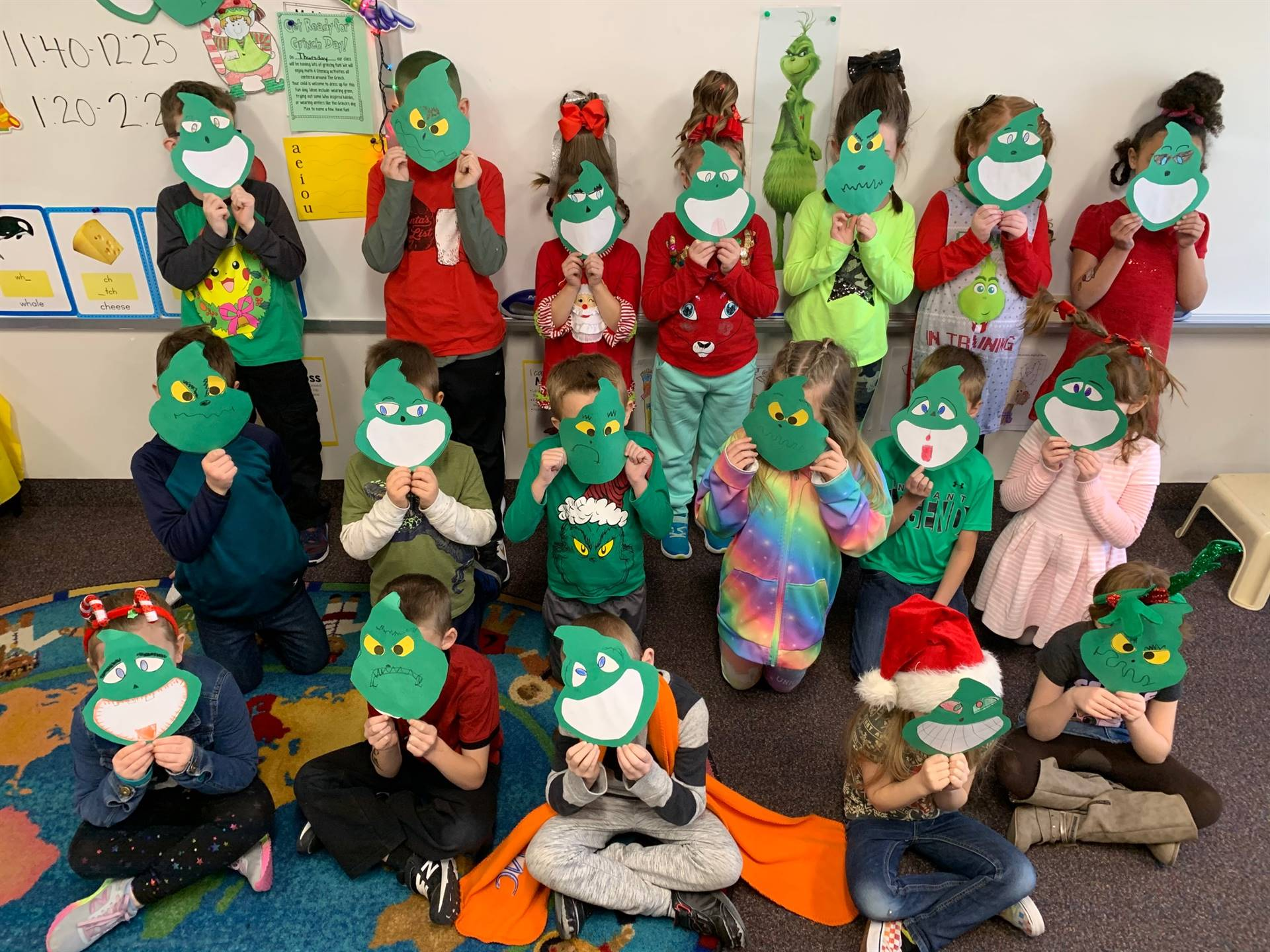 Students holding up their Grinch masks