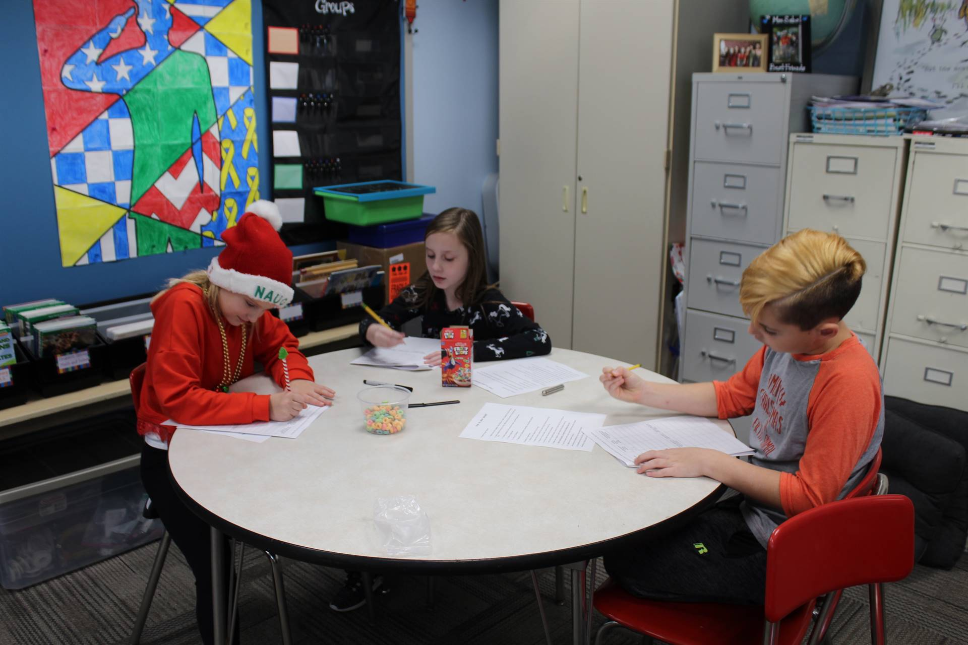 Three students writing their observations on worksheets