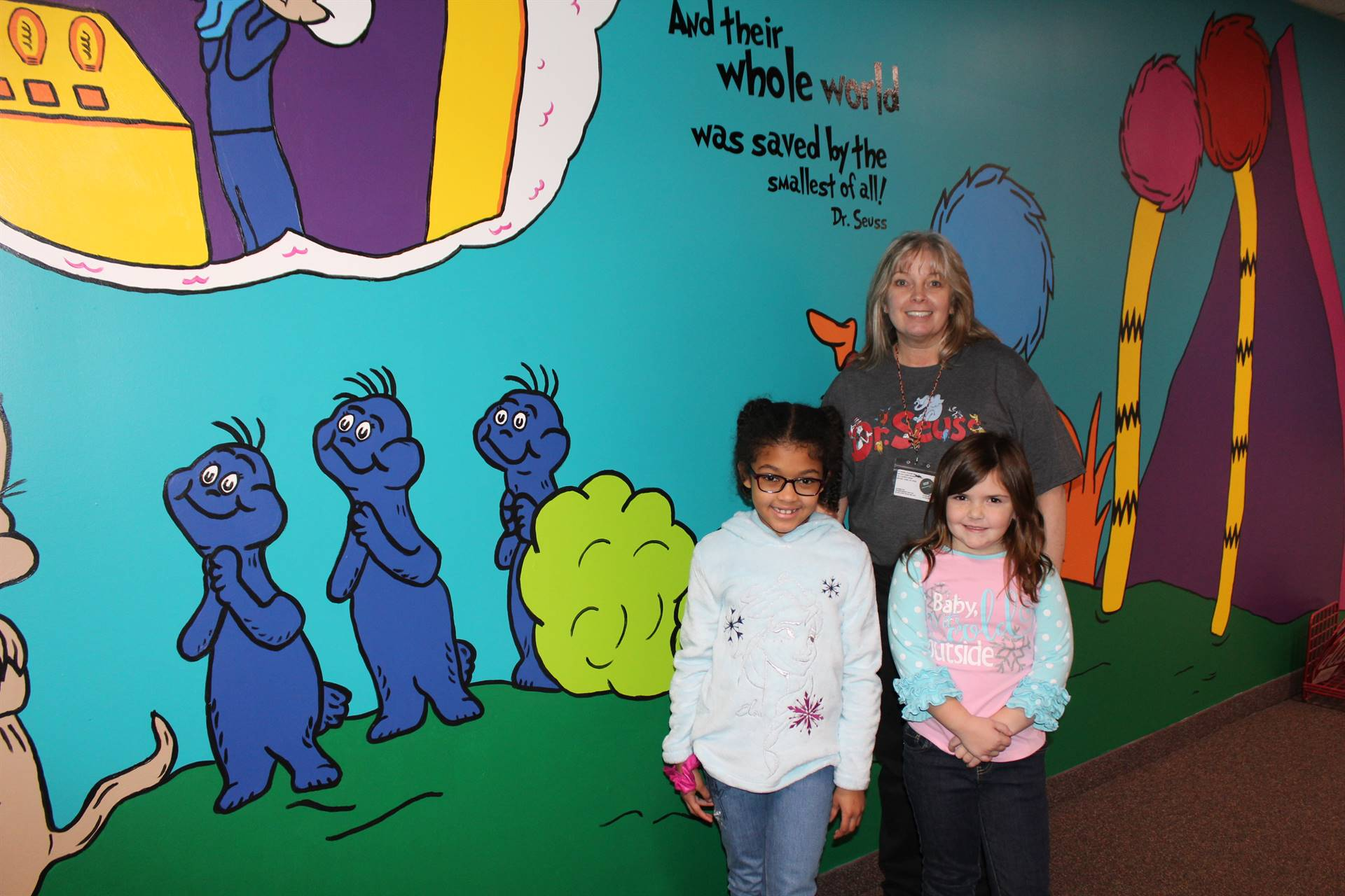 Mrs. Eckert-Graffam and two students in front of the wall
