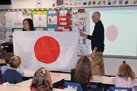 Two people holding up a Japanese flag