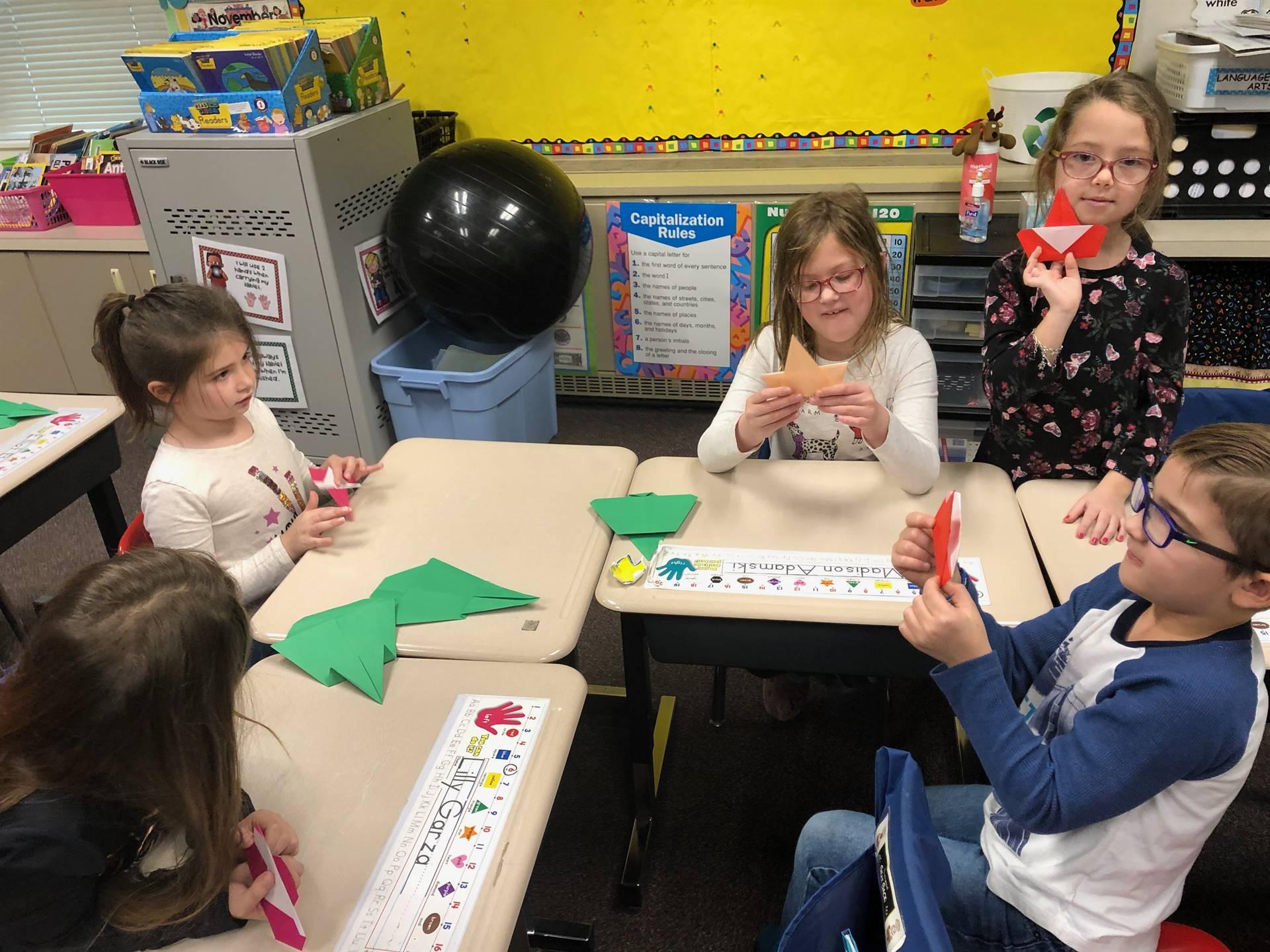 Five students making origami Christmas trees and Santas