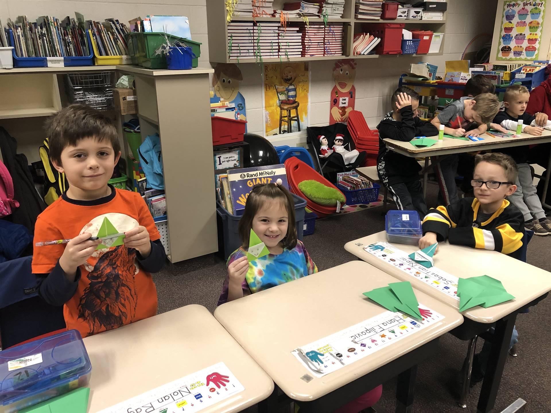 Three students making origami Christmas trees