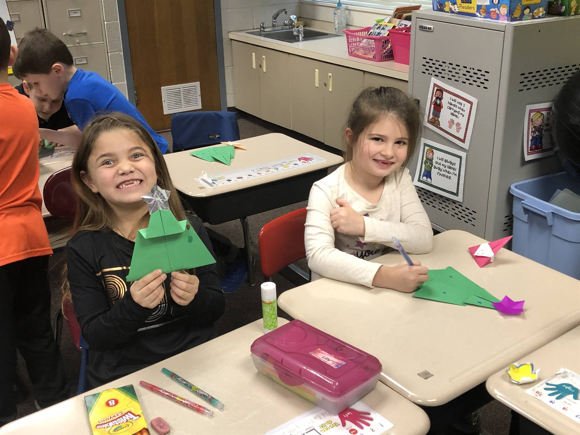 Two students making origami Christmas trees