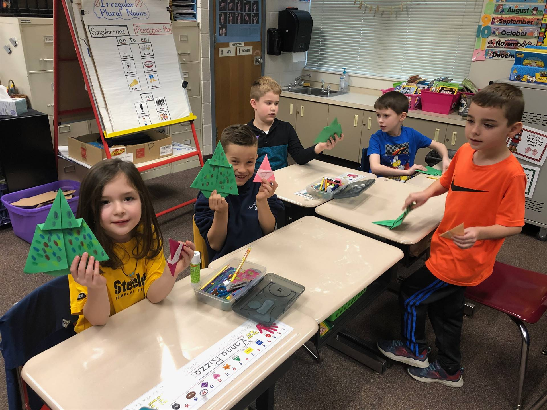 Five students making origami Christmas trees