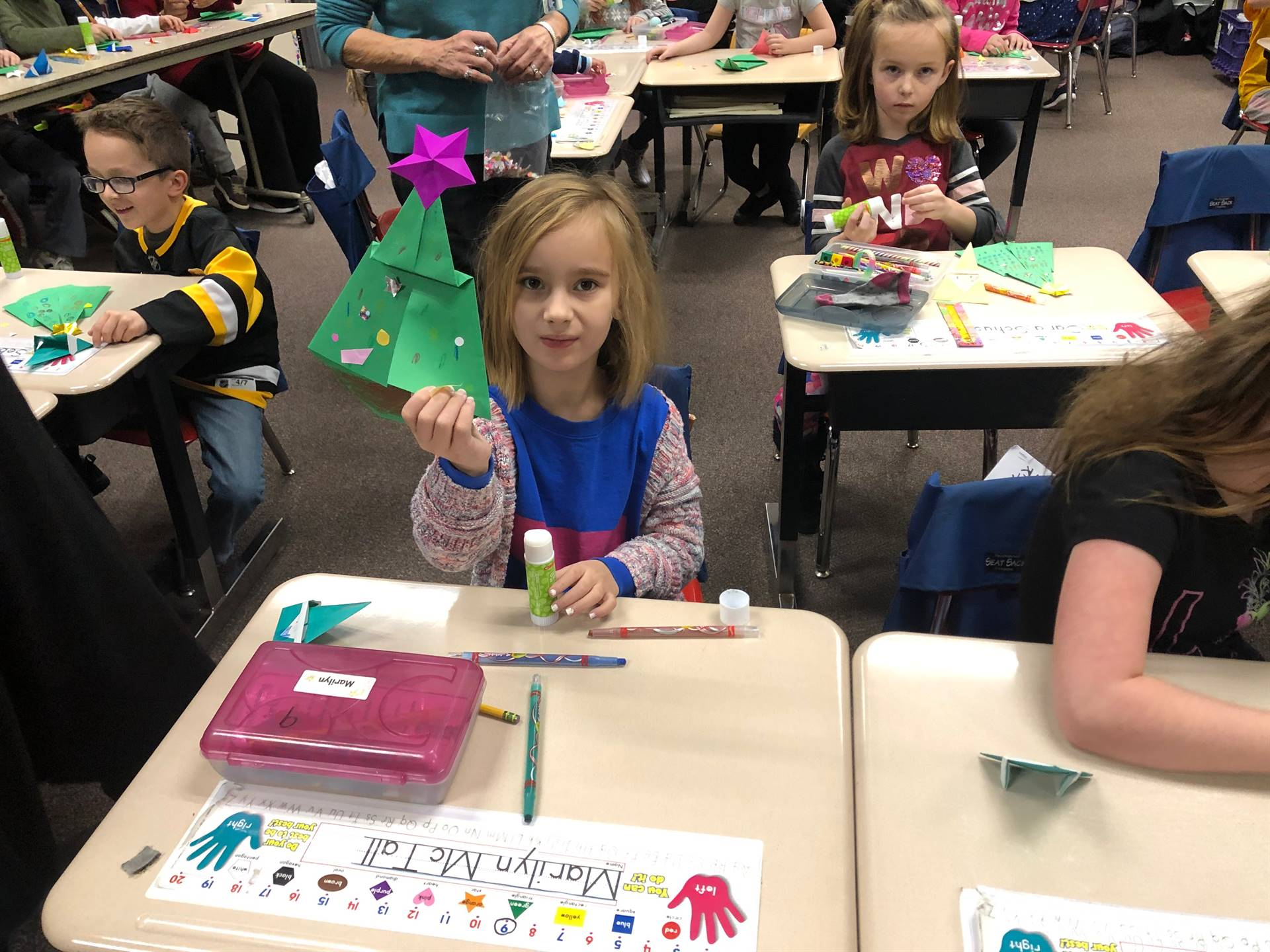 Student holding up her origami Christmas tree