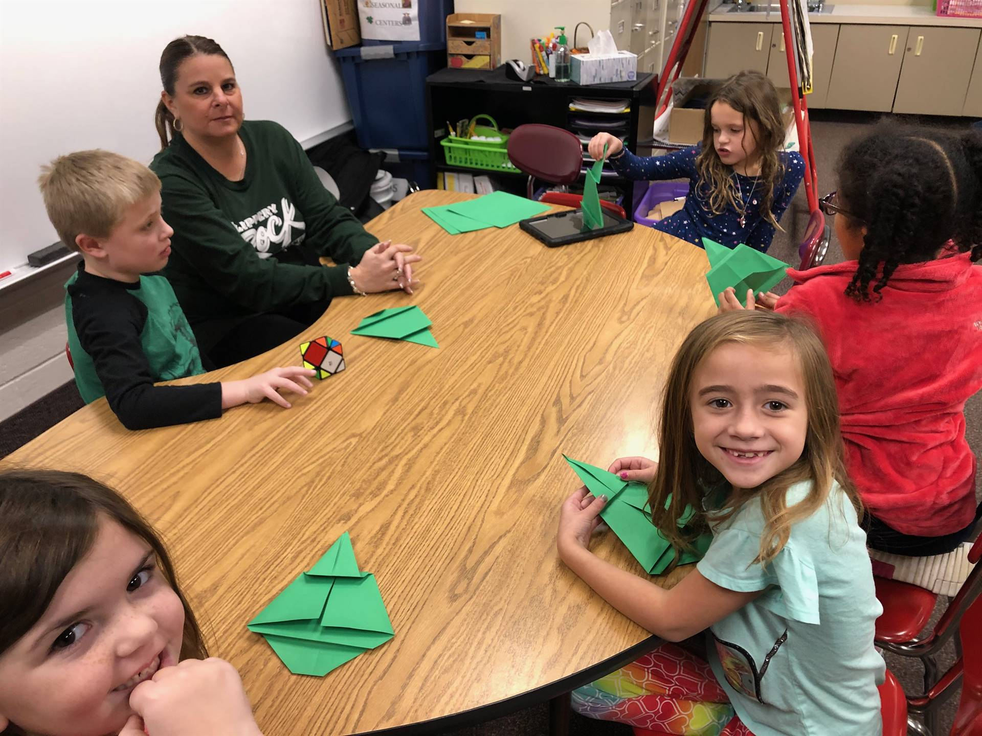 Students sitting around a table making origami Christmas trees