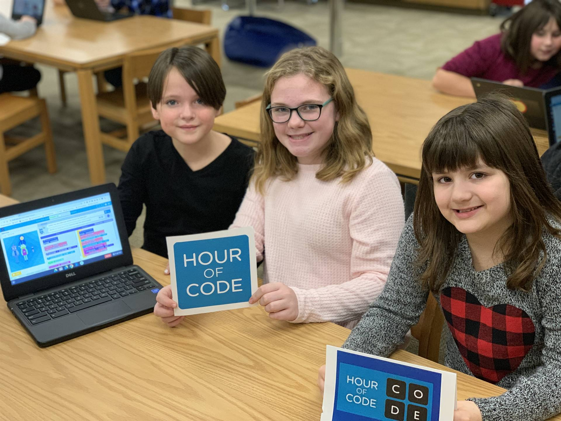 Three students with a computer