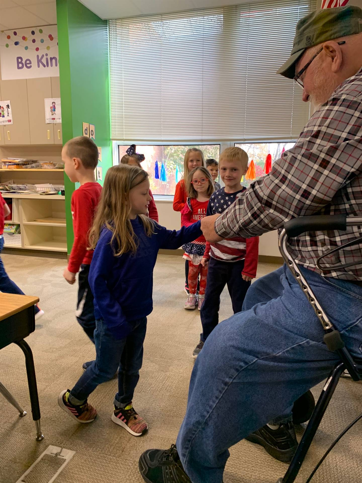 Students shaking veteran's hand