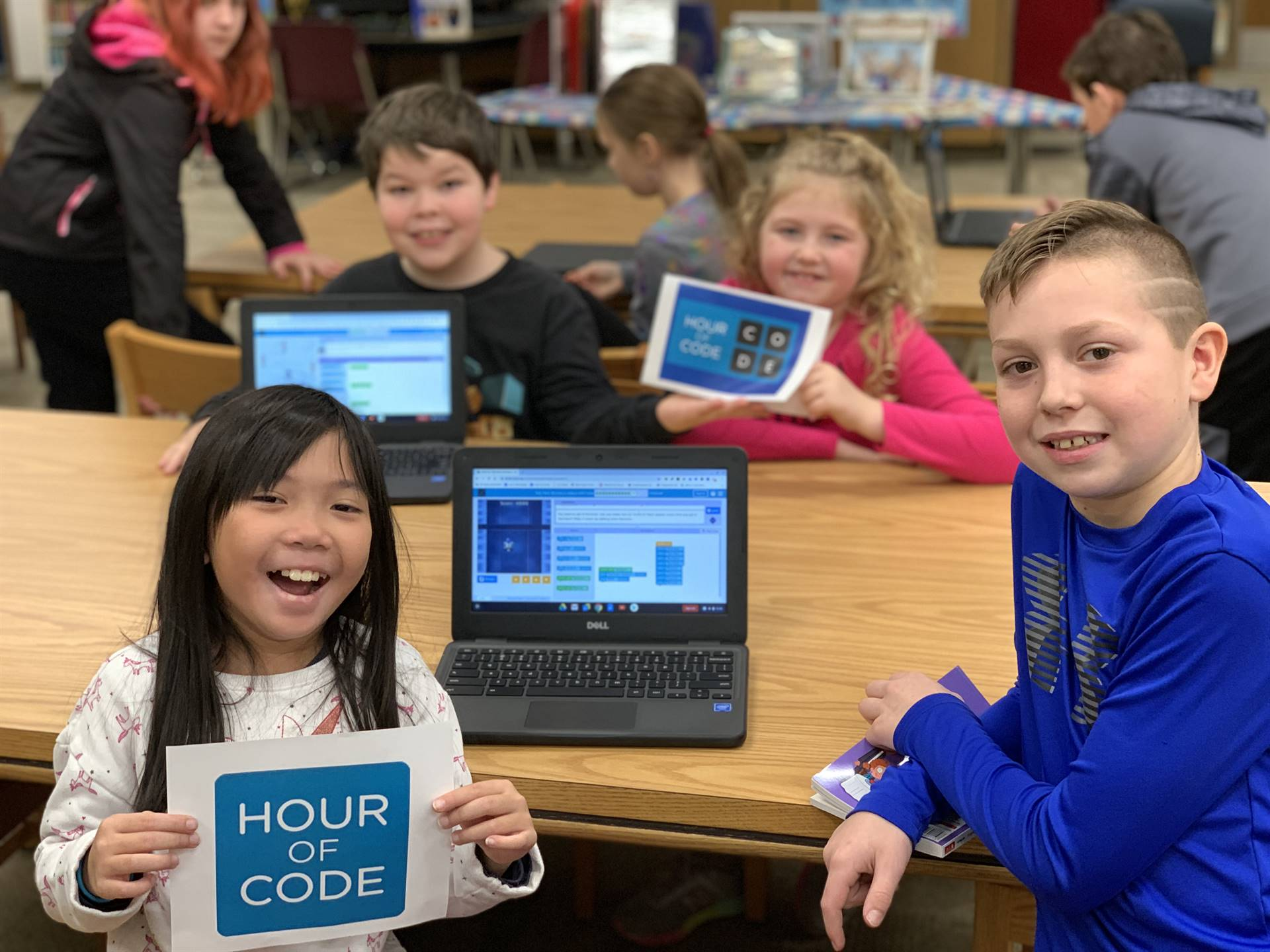 Four students with Hour of Code signs and computers