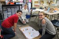 Three students making a hockey rink