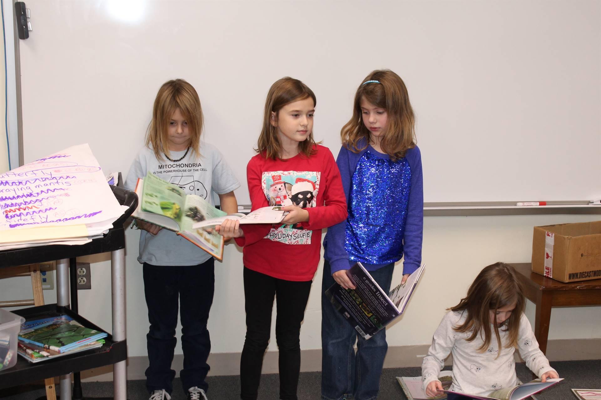 three students holding books