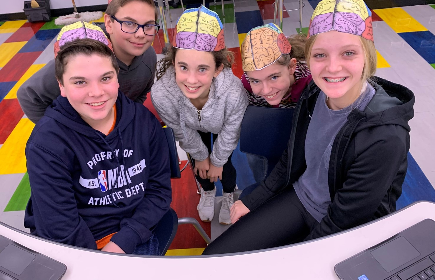 Five students wearing brain hats