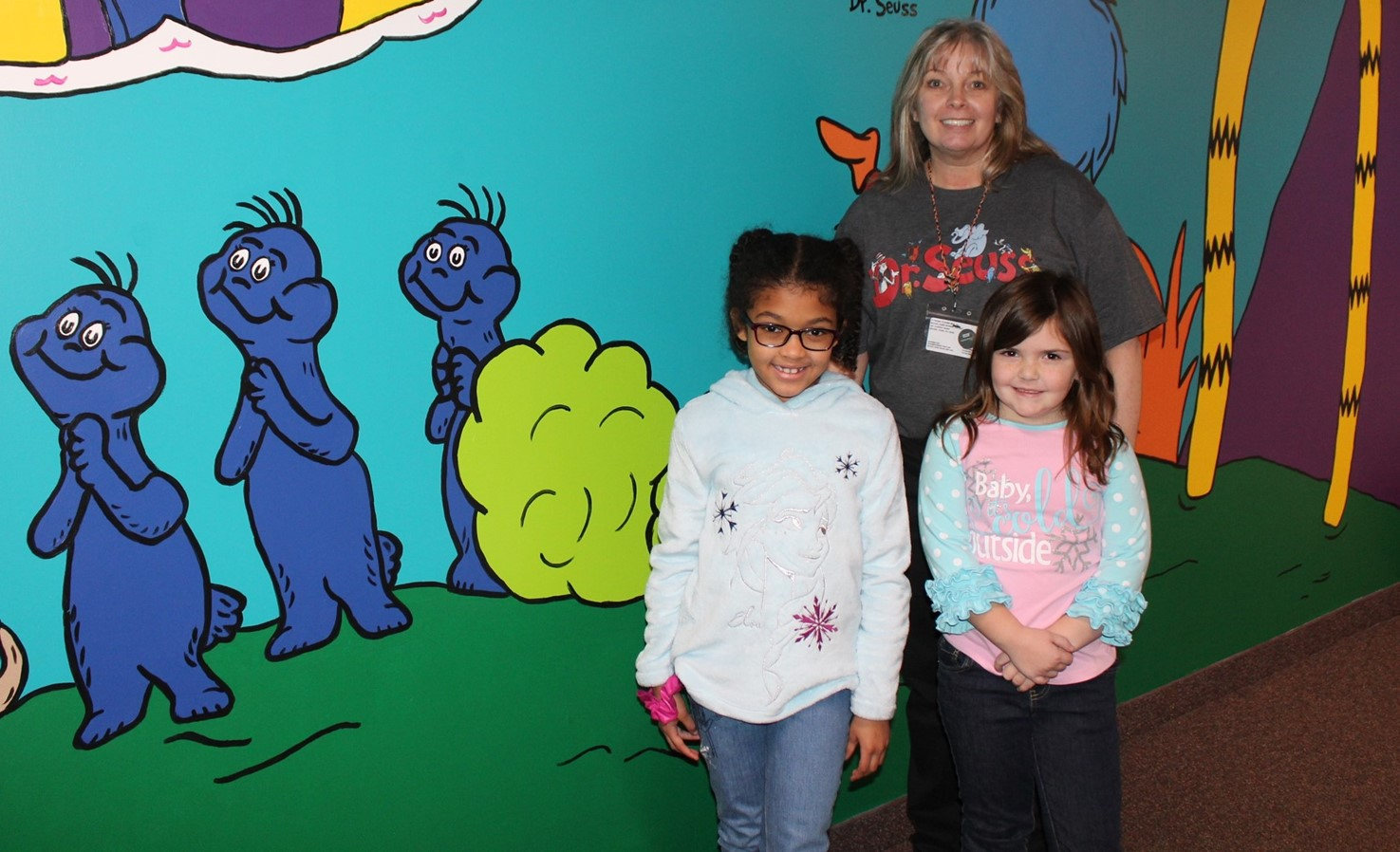 Teacher and two students in front of the mural