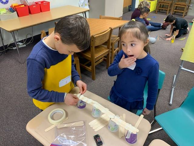 Two students working together to build a bridge