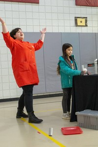 Student doing an experiment while an adult throws her arms in the air