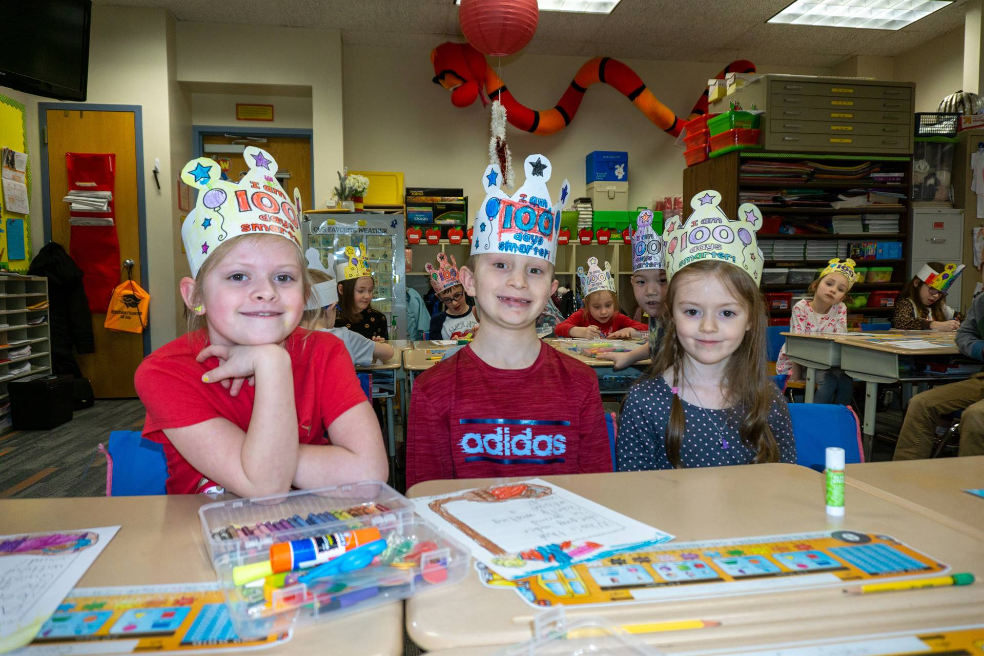 Three students wearing 100th day of school paper crowns
