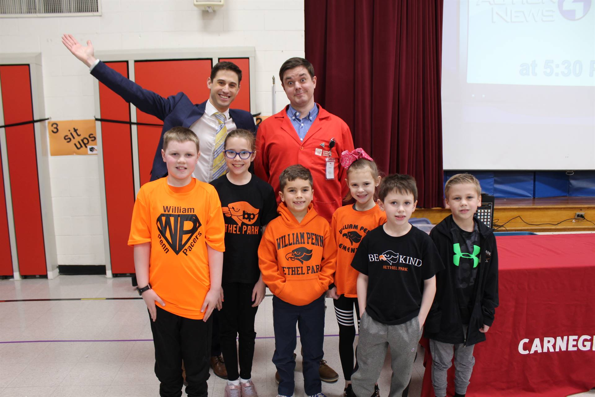 Six students with the two weather assembly presenters