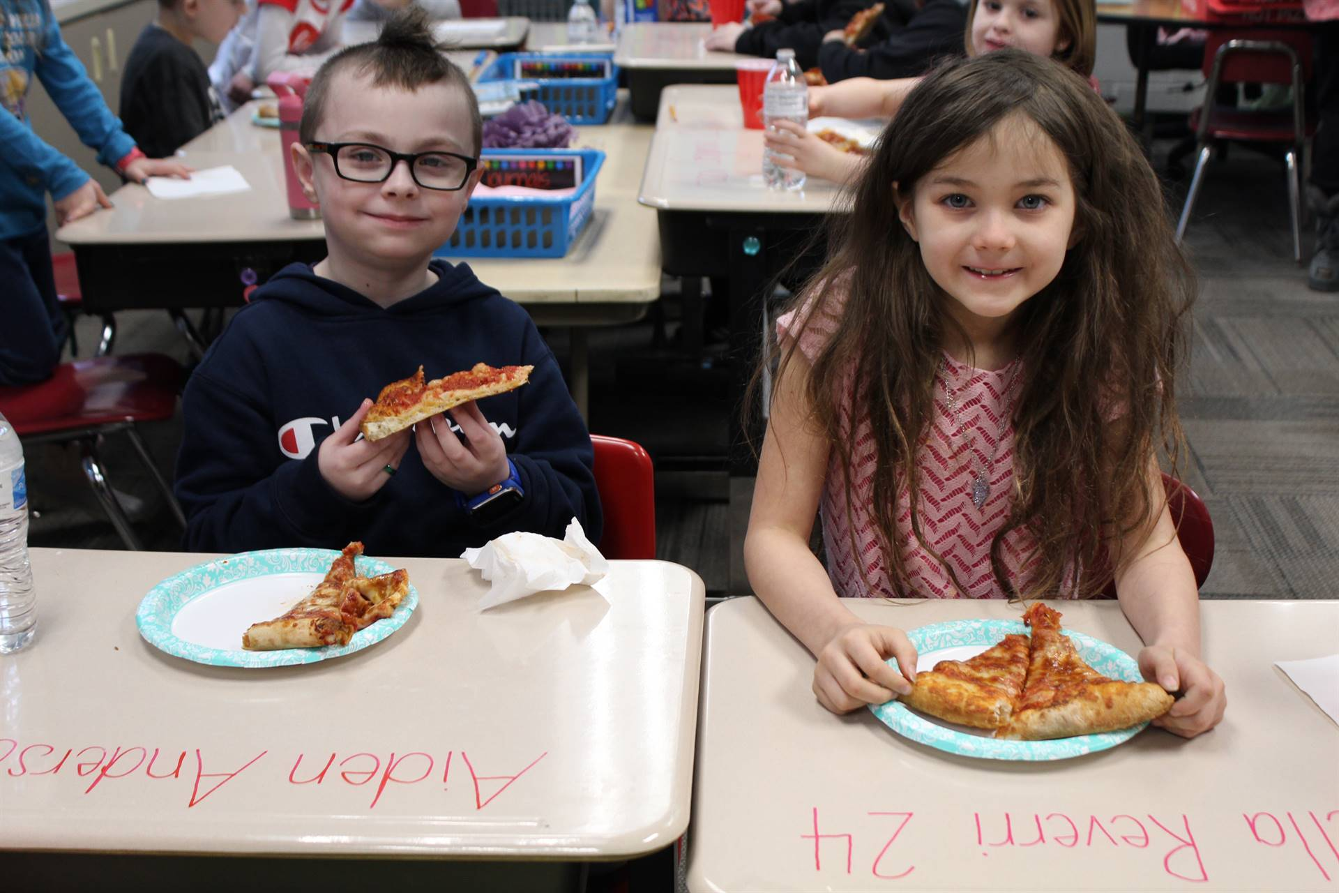 Two students eating pizza