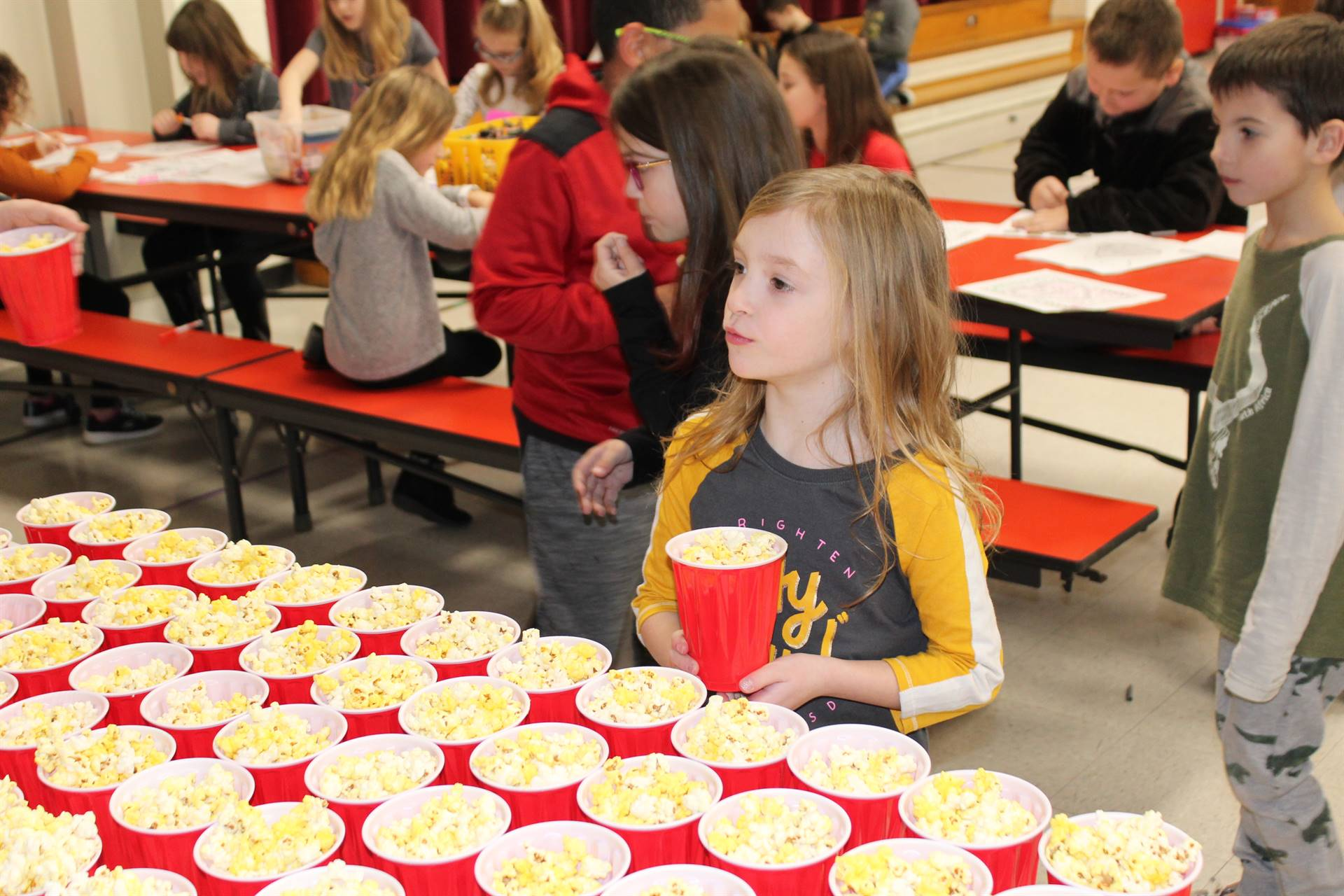 Student taking a cup of popcorn