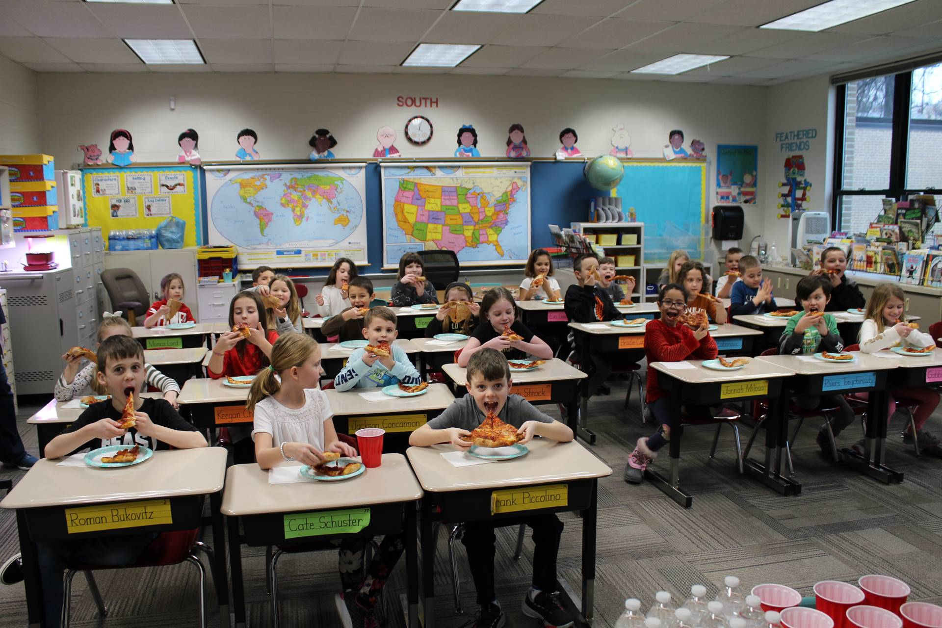 Classroom of students eating pizza