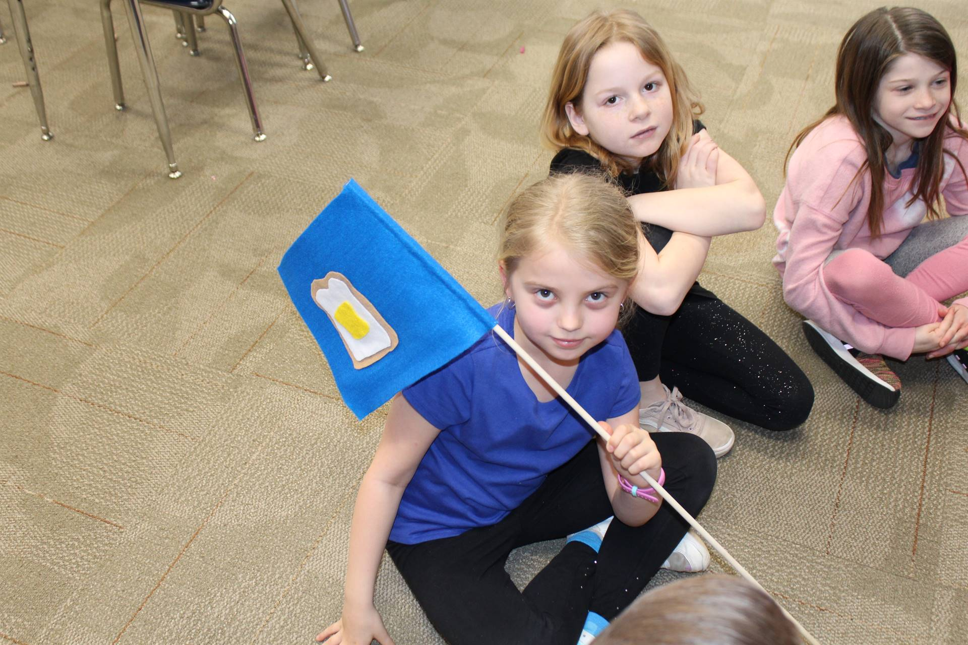 three students sitting on the floor