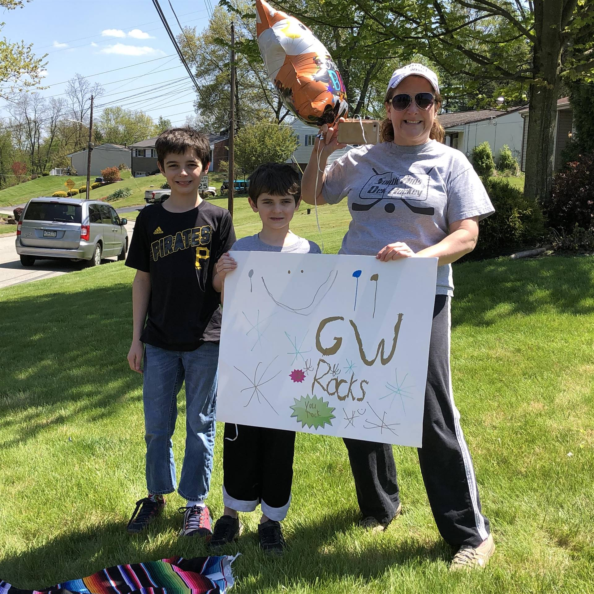 Mom and two students holding a sign