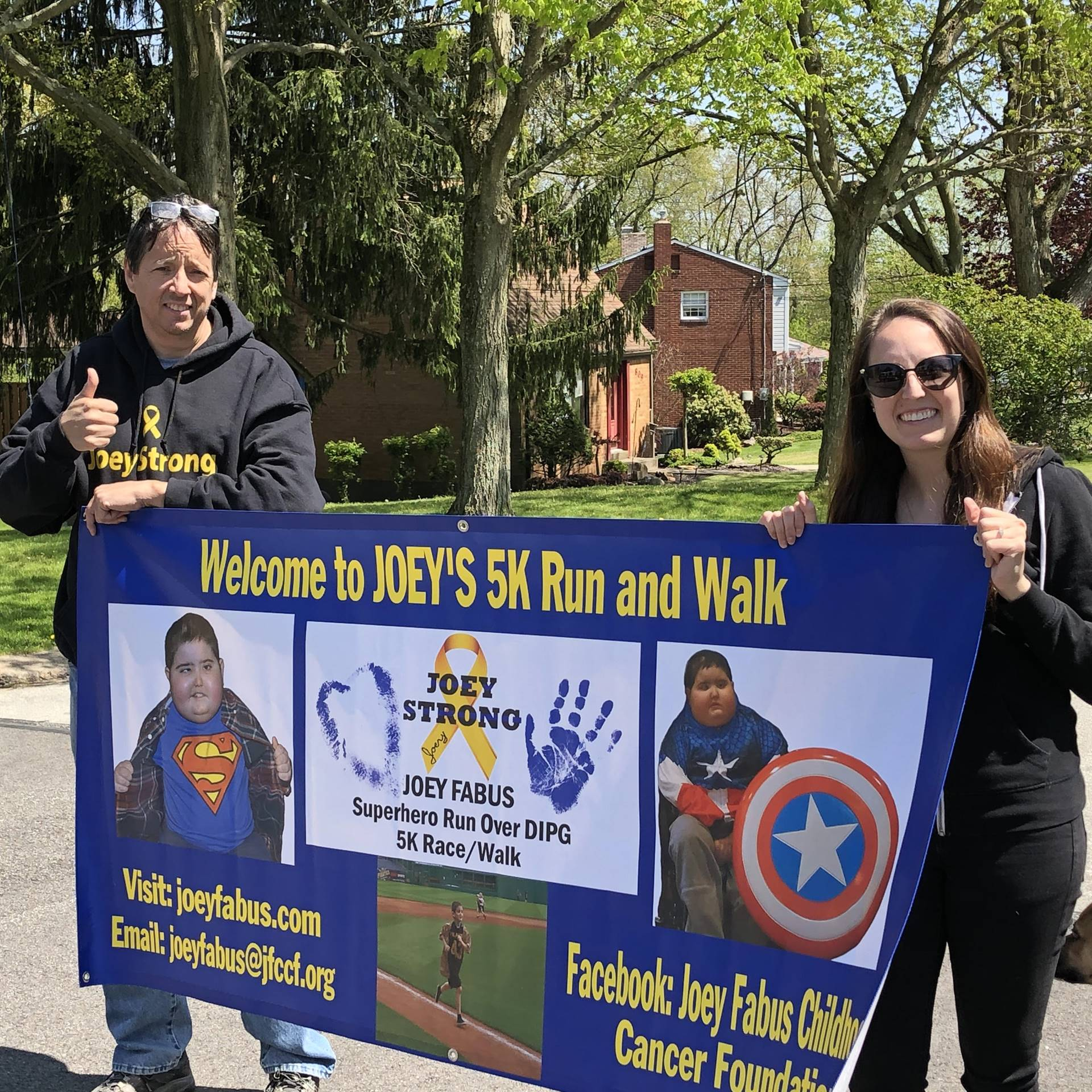 Two parents holding a banner